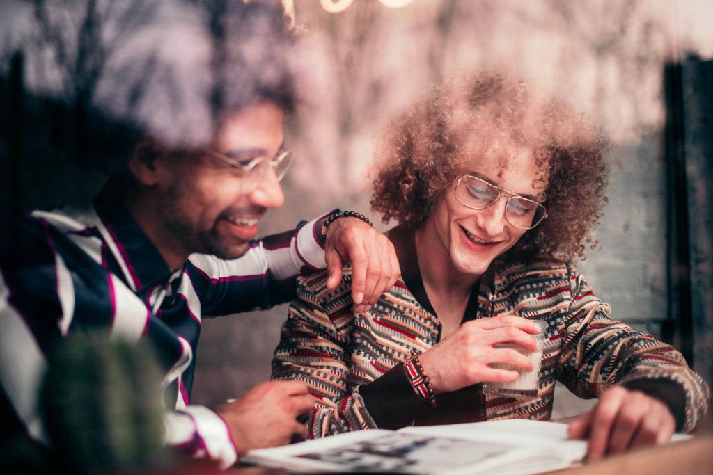 Content Creation Agentur: zwei stylische Männer lesen das Magazin der Content Creation Agentur: Fotografie von zwei lesenden Männern