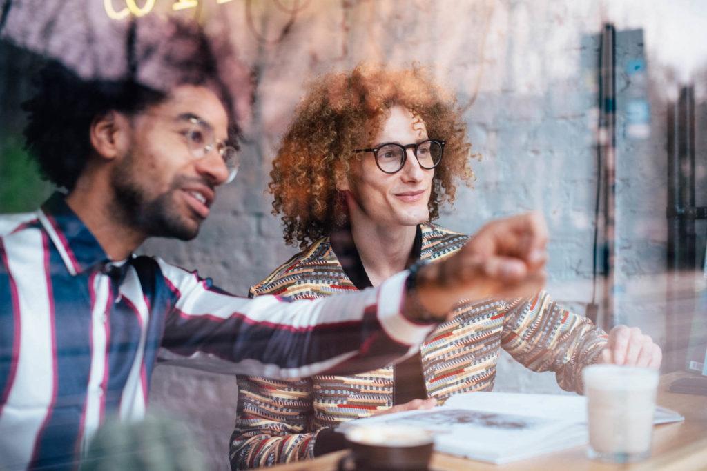 Content Creation: Fotografie zeigt zwei stylische Männer sitzen im Café