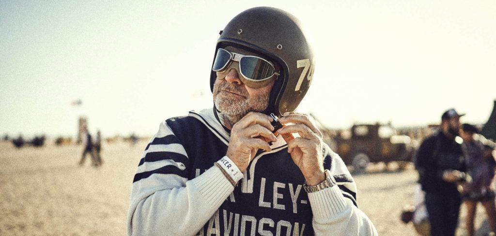 Beratung im Marketing: Ein Motorrad-Rennfahrer setzt seinen Helm auf