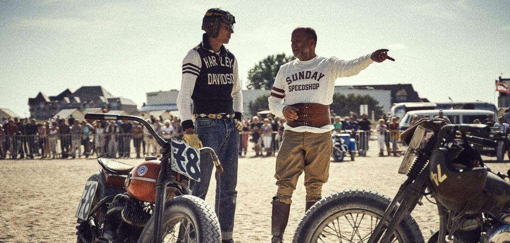 Agentur für Marketingberatung zeigt auf diesem Bild zwei Motorrad-Rennfahrer im Austausch