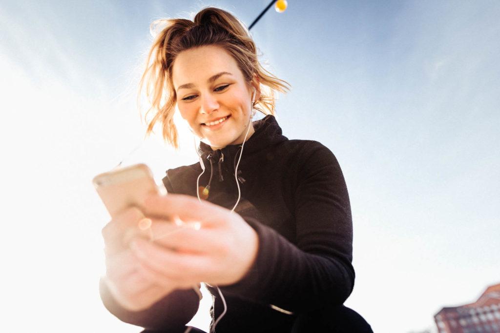 Content Creation Agentur: eine Frau liest Social Media auf ihrem Smartphone