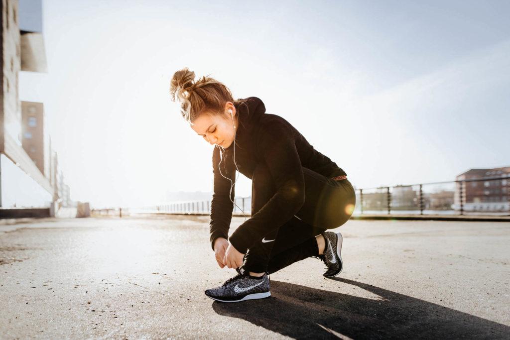 Social Media Content der Agentur aus Berlin: eine Frau bindet zum Joggen ihre Schuhe zu